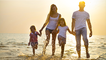 Perhe rannalla.